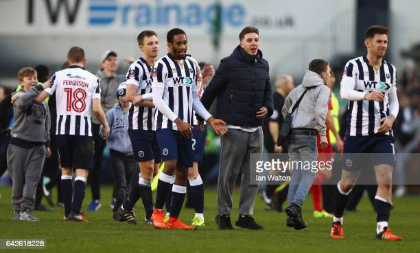 Shaun Cummings of Millwall celerates with a Millwall fan on the pitch after The Emirates FA Cup Fifth Round match between Millwall and Leicester City...