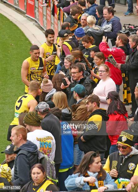 Shaun Grigg of the Tigers and Trent Cotchin of the Tigers sign autographs for supporters in the crowd after a Richmond Tigers AFL training session at...
