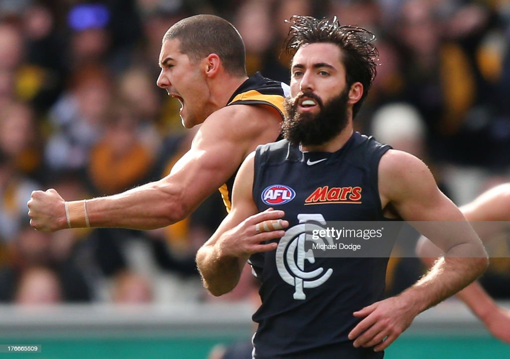 Shaun Grigg of the Tigers celebrates a goal next to Kade Simpson of the Blues during the round 21 AFL match between the Richmond Tigers and the Carlton Blues at Melbourne Cricket Ground on August 17, 2013 in Melbourne, Australia.