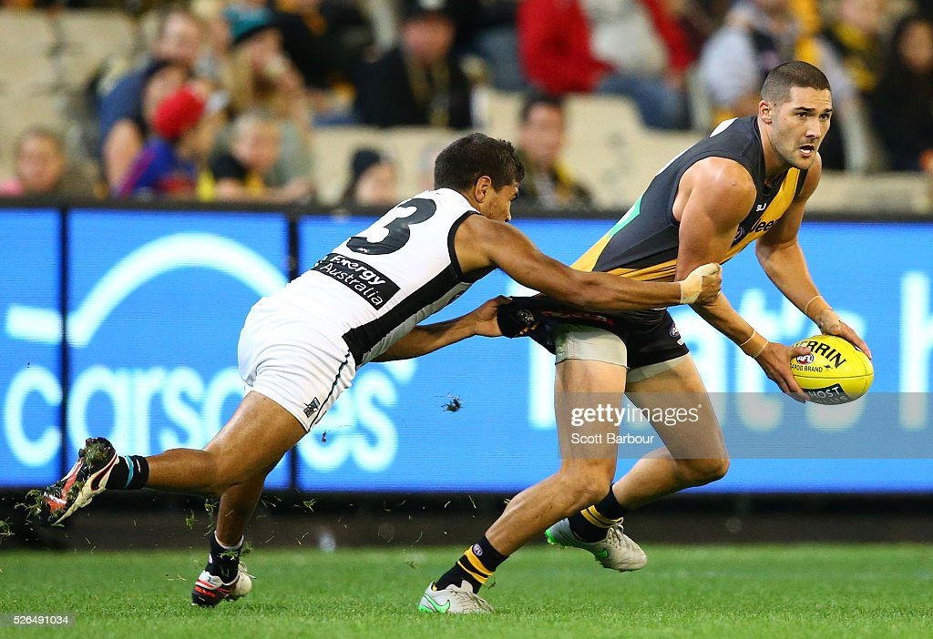 Shaun Grigg of the Tigers is tackled by Jake Neade of the Power during the round six AFL match between the Richmond Tigers and the Port Adelaide Power at Melbourne Cricket Ground on April 30, 2016 in Melbourne, Australia.