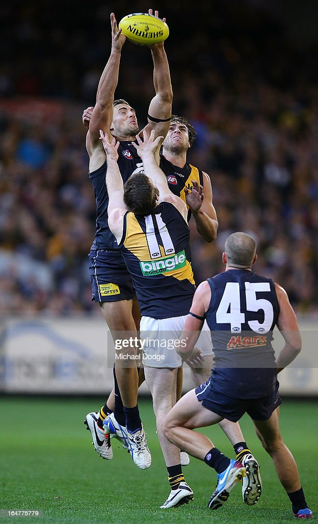 A Shaun Hampson of the Blues marks the ball against Jake Batchelor and Ben Griffiths of the Tigers during the round one AFL match between the Carlton Blues and the Richmond Tigers at Melbourne Cricket Ground on March 28, 2013 in Melbourne, Australia.