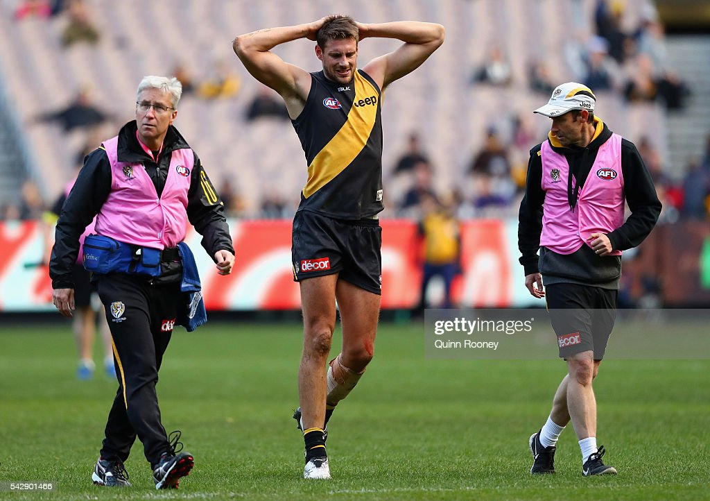 Shaun Hampson of the Tigers is helped from the ground by trainers after injuring his knee during the round 14 AFL match between the Richmond Tigers and the Brisbane Lions at Melbourne Cricket Ground on June 25, 2016 in Melbourne, Australia.