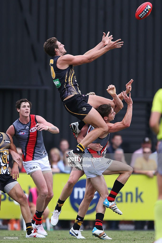 Shaun Hampson of the Tigers marks the ball high over Jake Melksham of the Bombers during an AFL Practice Match between the Richmond Tigers and the Essendon Bombers at Punt Road Oval on March 7, 2014 in Melbourne, Australia.