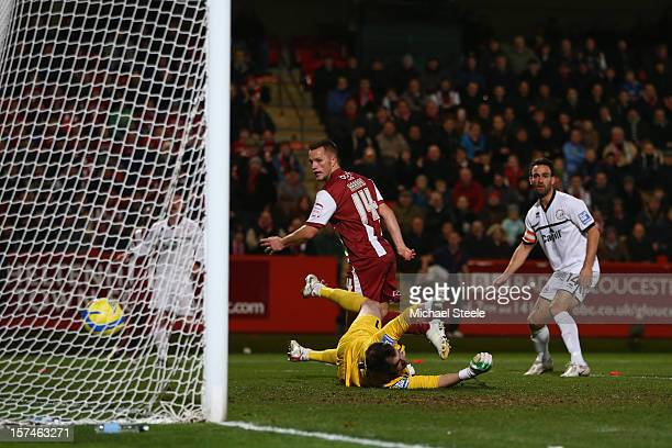 Shaun Harrad of Cheltenham Town scores the opening goal past goalkeeper James Bittner of Hereford United during the FA Cup with Budweiser Second...