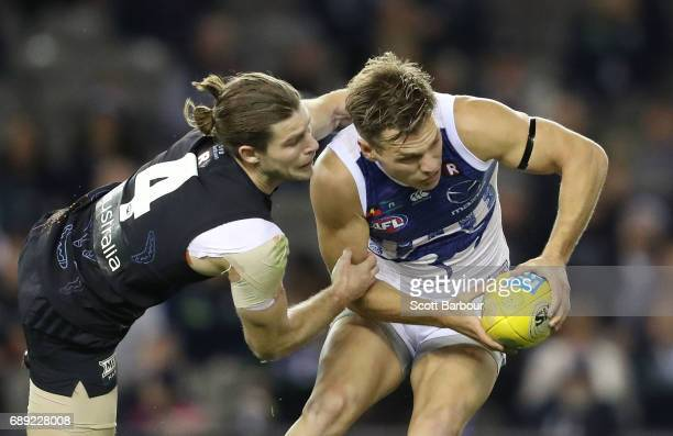 Shaun Higgins of the Kangaroos beats the tackle of Bryce Gibbs of the Blues during the round 10 AFL match between the Carlton Blues and the North...