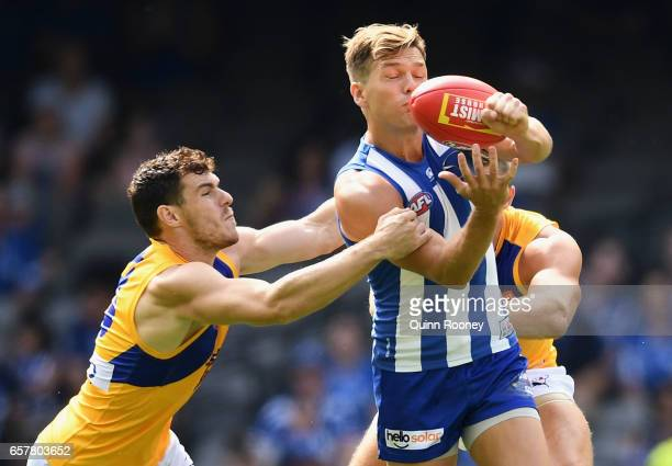 Shaun Higgins of the Kangaroos handballs whilst being tackled by Luke Shuey of the Eagles during the round one AFL match between the North Melbourne...
