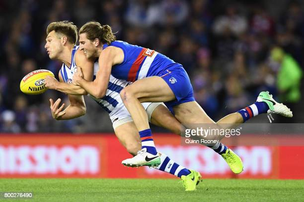 Shaun Higgins of the Kangaroos handballs whilst being tackled by Marcus Bontempelli of the Bulldogs during the round 14 AFL match between the Western...