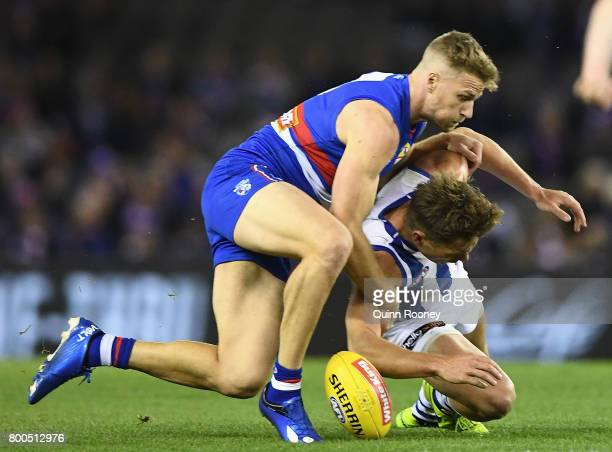 Shaun Higgins of the Kangaroos is tackled by Jake Stringer of the Bulldogs during the round 14 AFL match between the Western Bulldogs and the North...