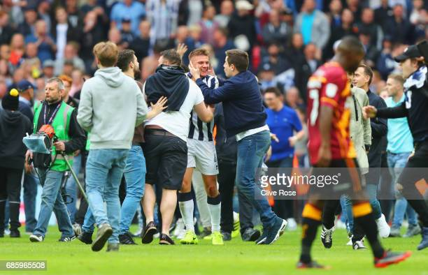Shaun Hutchinson of Millwall is mobbed by Millwall fans as they invade the pitch in celebration after the Sky Bet League One Playoff Final between...