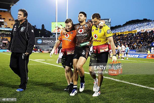 Shaun Johnson of the Warriors is carried off the field after picking up an injury to his leg during the round 20 NRL match between the New Zealand...