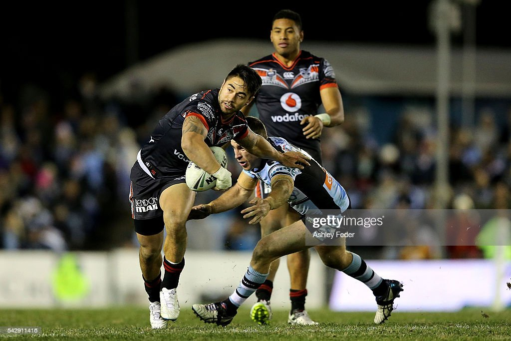 Shaun Johnson of the Warriors is tackled by the Sharks defence during the round 16 NRL match between the Cronulla Sharks and the New Zealand Warriors at Southern Cross Group Stadium on June 25, 2016 in Sydney, Australia.