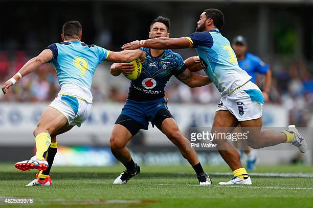 Shaun Johnson of the Warriors is tackled during the match between the Warriors and the Titans in the 2015 Auckland Nines at Eden Park on January 31...