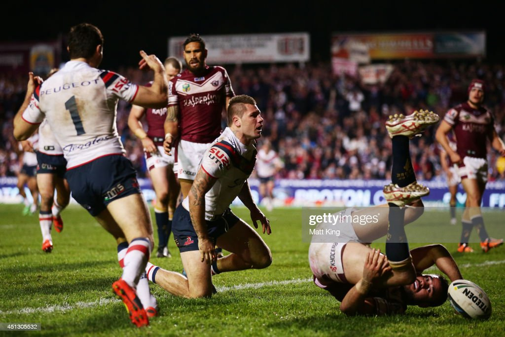 Shaun Kenny-Dowall of the Roosters scores a try as Justin Horo of the Sea Eagles flips over during the round 16 NRL match between the Manly Warringah Sea Eagles and the Sydney Roosters at Brookvale Oval on June 27, 2014 in Sydney, Australia.