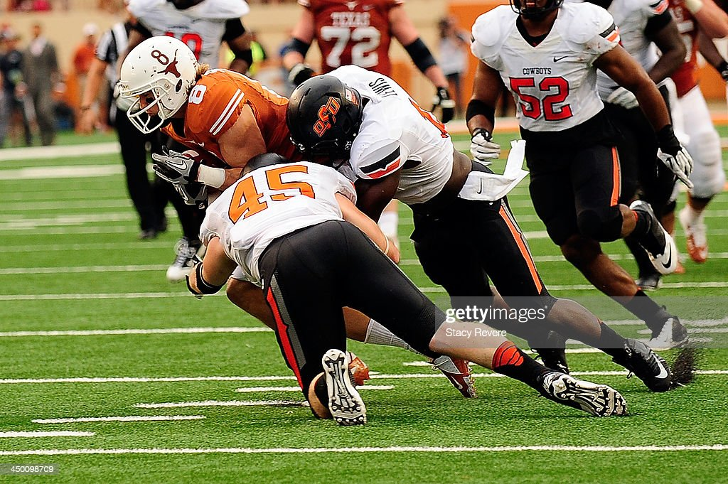 Shaun Lewis #11 and Caleb Lavey #45 of the Oklahoma State Cowboys bring down Jaxon Shipley #8 of the Texas Longhorns during a game at Darrell K Royal-Texas Memorial Stadium on November 16, 2013 in Austin, Texas. Oklahoma State won the game 38-13.