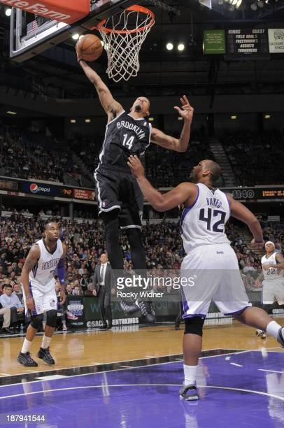 Shaun Livingston of the Brooklyn Nets dunks the ball against Chuck Hayes of the Sacramento Kings at Sleep Train Arena on November 13 2013 in...