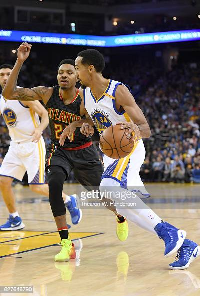 Shaun Livingston of the Golden State Warriors drives towards the basket with the ball against Kent Bazemore of the Atlanta Hawksduring an NBA...