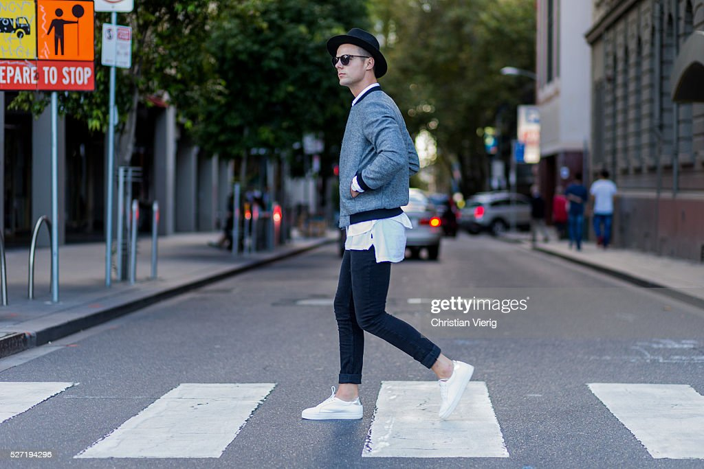 Shaun Lyle wearing a grey Topman college jacket, a black hat and sunglasses, a long white Topman tshirt, black Topman jeans, white Senso sneakers on May 2, 2016 in Melbourne, Australia
