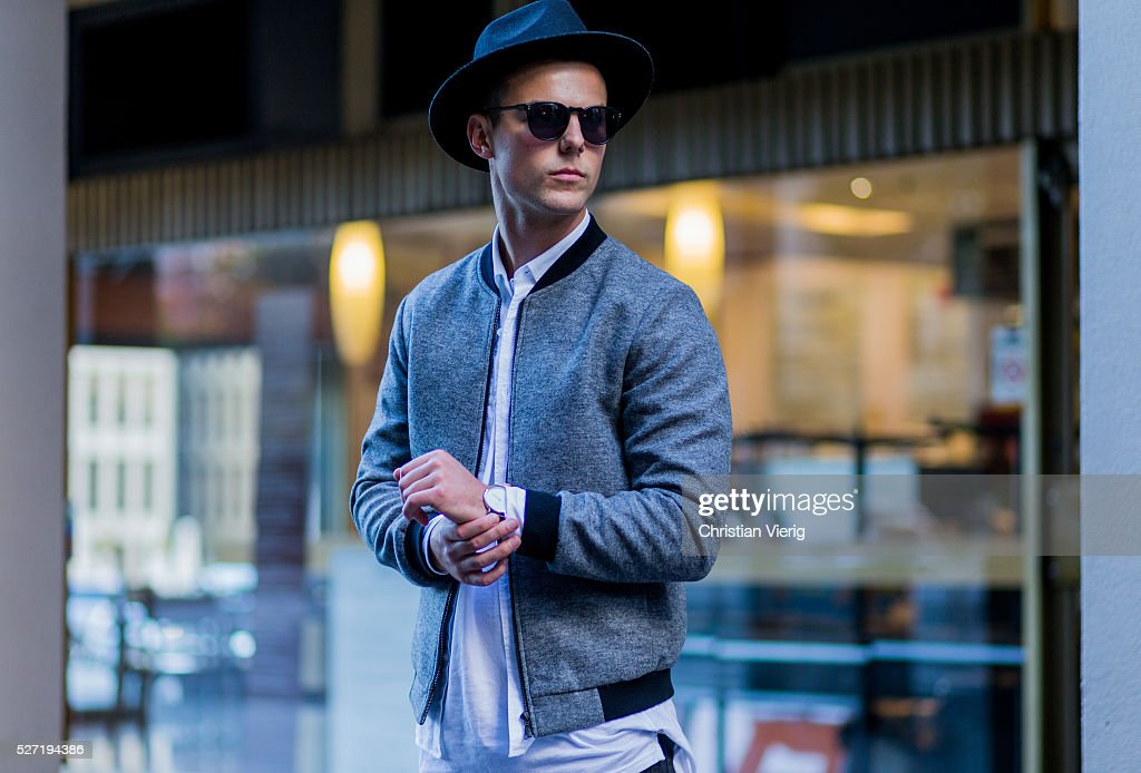 Shaun Lyle wearing a grey Topman college jacket, a black hat and sunglasses, a long white Topman tshirt, black Topman jeans while checking his watch on May 2, 2016 in Melbourne, Australia