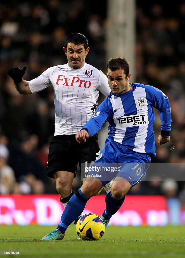 Shaun Maloney of Wigan is pursued by <a gi-track='captionPersonalityLinkClicked' href=/galleries/search?phrase=Giorgos+Karagounis&family=editorial&specificpeople=240229 ng-click='$event.stopPropagation()'>Giorgos Karagounis</a> of Fulham during the Barclays Premier League match between Fulham and Wigan Athletic at Craven Cottage on January 12, 2013 in London, England.