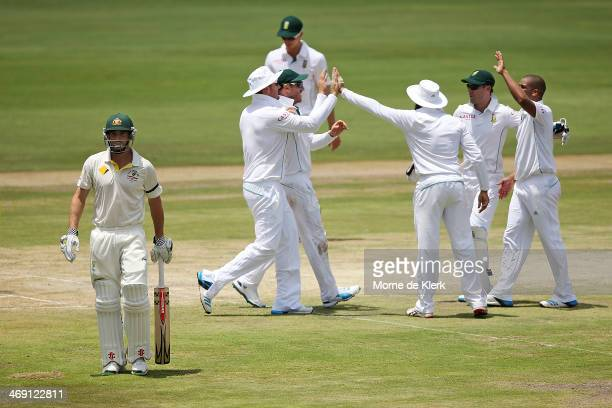 Shaun Marsh of Australia leaves the field after getting out to Vernon Philander of South Africa as South African players celebrate during day two of...