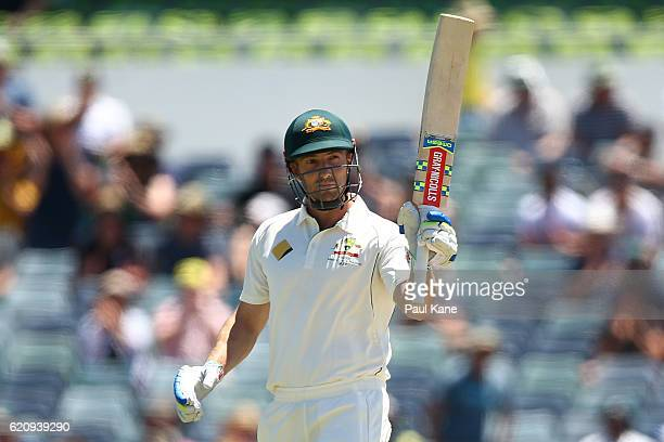 Shaun Marsh of Australia raises his bat to celebrate his half century during day two of the First Test match between Australia and South Africa at...