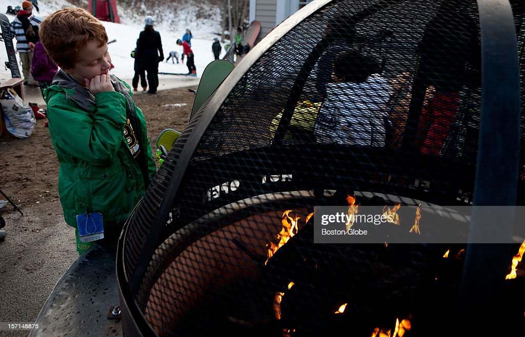 Shaun McCarty, 9, warms up at the outdoor fire pit at Loon Mountain Resort in Lincoln, New Hampshire on November 24, 2012.