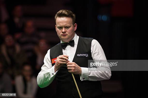 Shaun Murphy of England chalks the cue during his first round match against Barry Hawkins of England on day four of the Dafabet Masters at Alexandra...