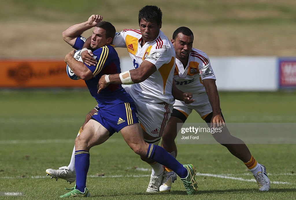Shaun Treeby of the Highlanders is tackled by Ross Filipo of the Chiefs during the 2013 Super Rugby pre-season friendly match between the Chiefs and the Highlanders at Owen Delany Park, Taupo on February 2, 2013 in Taupo, New Zealand.
