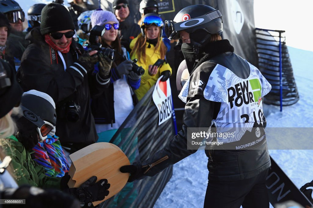 Shaun White (R) gives his second place trophy to young fan Connor Tripp, 11, of Castle Rock, Colorado, following the men's snowboard superpipe final at the Dew Tour iON Mountain Championships on December 14, 2013 in Breckenridge, Colorado.