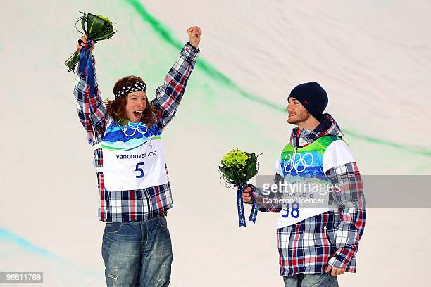 Shaun White of the United States reacts after winning the gold and Scott Lago after winning the bronze during the flower ceremony for the Snowboard...