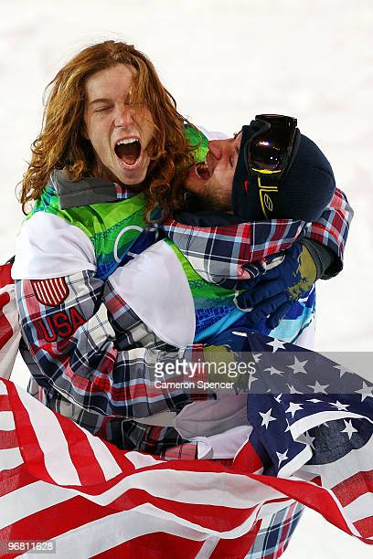 Shaun White of the United States reacts with fellow American Scott Lago after White wins the gold medal and Lago the bronze in the Snowboard Men's...