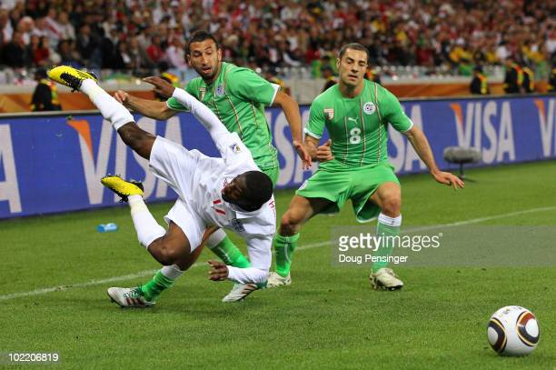 Shaun Wright Phillips of England is tackled by Nadir Belhadj and Medhi Lacen of Algeria during the 2010 FIFA World Cup South Africa Group C match...