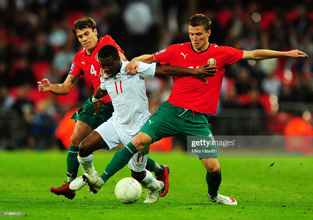 Shaun WrightPhillips of England battles with Timofey Kalachev and Igor Shitov of Belarus during the FIFA 2010 World Cup Qualifying Group 6 match...