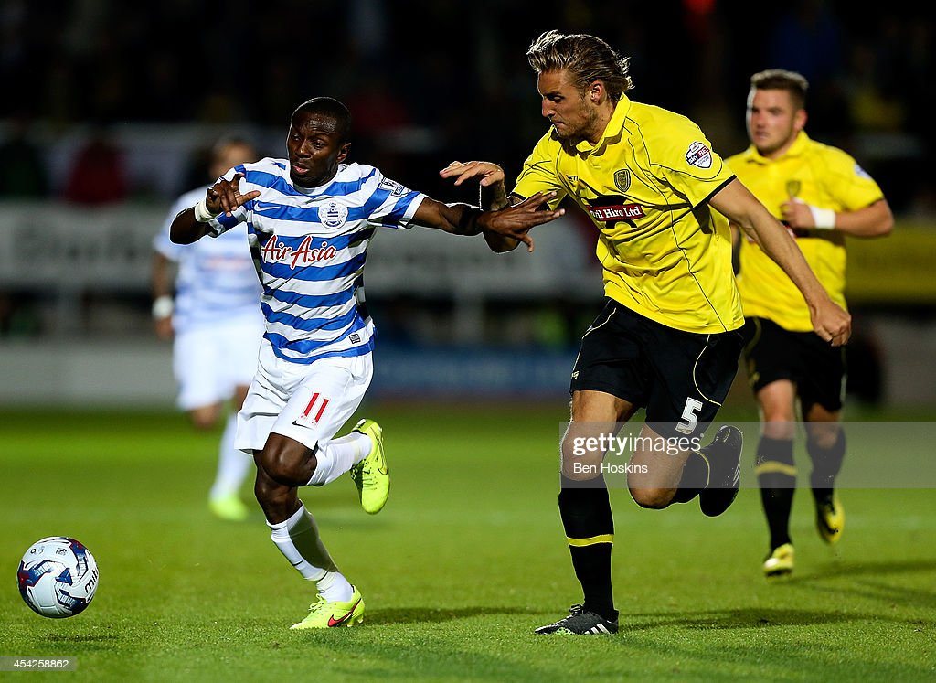 Shaun WrightPhillips of QPR holds off the challenge of George Taft of Burton during the Capital One Cup Second Round match between Burton Albion and...