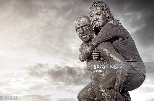 Shaved man carrying female friend during a mud run