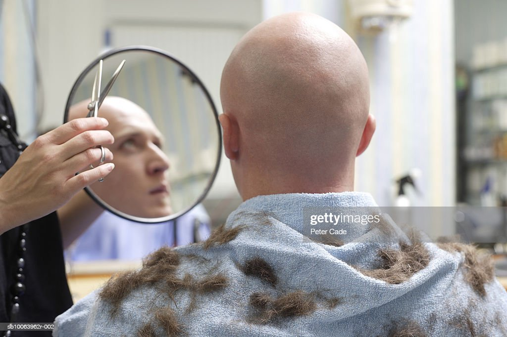 Shaved man with hairdresser at barber shop, rear view : Stock Photo