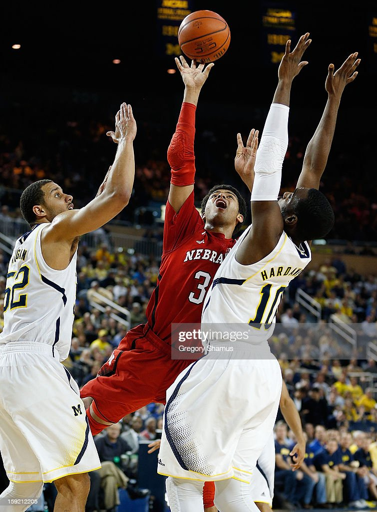 Shavon Shields #31 of the Nebraska Cornhuskers gets off a second half shot between Tim Hardaway Jr. #10 and Jordan Morgan #52 of the Michigan Wolverines at Crisler Center on January 9, 2013 in Ann Arbor, Michigan. Michigan won the game 62-47.