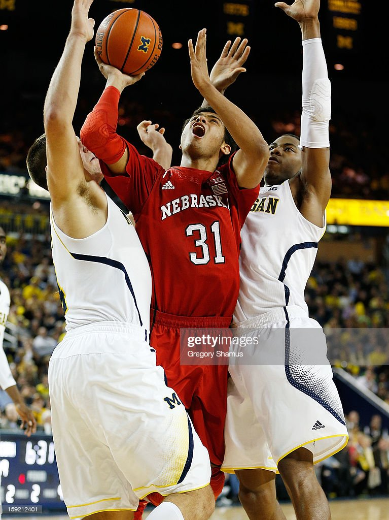 Shavon Shields #31 of the Nebraska Cornhuskers gets off a second half shot between Mitch McGary #4 and Caris LeVert #23 of the Michigan Wolverines at Crisler Center on January 9, 2013 in Ann Arbor, Michigan. Michigan won the game 62-47.