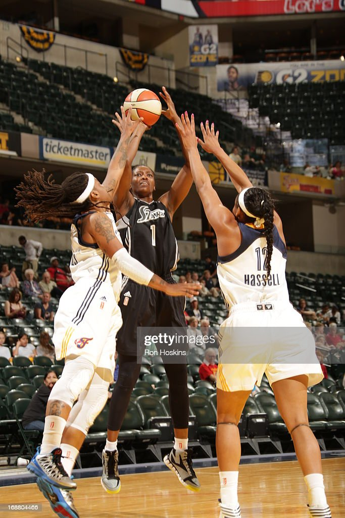 Shavonte Zellous #1 and Jasmine Hassell #12 of the Indiana Fever try to block the shot of DeLisha Milton-Jones #1 of the San Antonio Silver Stars on May 13, 2013 at Bankers Life Fieldhouse in Indianapolis, Indiana.