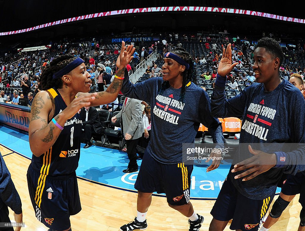 Shavonte Zellous #1 of the Indiana Fever celebrates with Lynetta Kizer #11 and Natasha Howard #33 (L-R) after the game against the Atlanta Dream on July 1, 2014 at Philips Arena in Atlanta, Georgia.
