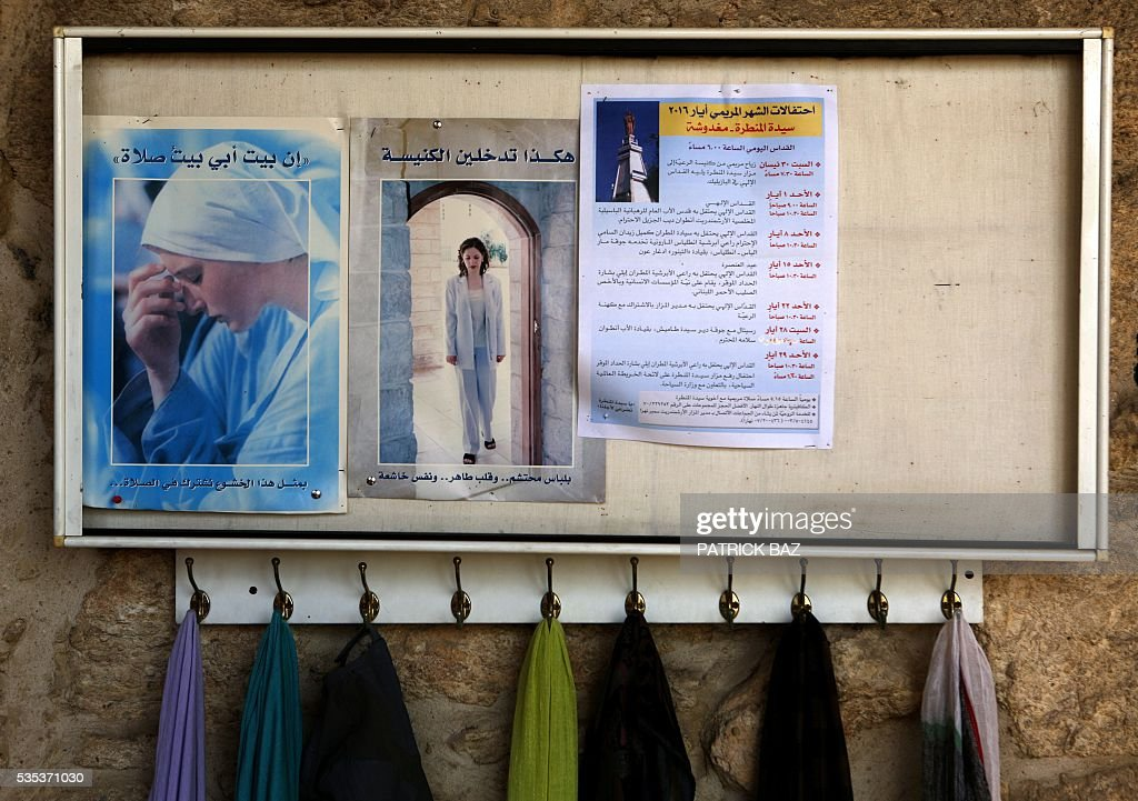 Shawls hang under leaflets in Arabic, advising women how to dress decently when entering the Grotto of Our Lady of Mantara, in the southern Lebanese town of Maghdouche East of Sidon, on May 29, 2016, during an event by the Ministry of Tourism to put the Grotto of Maghdouche on the international religious tourism map. Magdouche, along with Lourdes in France, Fatima in Portugal and Medugorje in Bosnia & Herzegovina are expected to be put on the international religious tourism map. According to local tradition the Virgin Mary accompanied Jesus during his journey to Tyre and to Sidon and waited for him in the grotto at Magdoucheh. The grotto was discovered 400 years ago. / AFP / Patrick BAZ