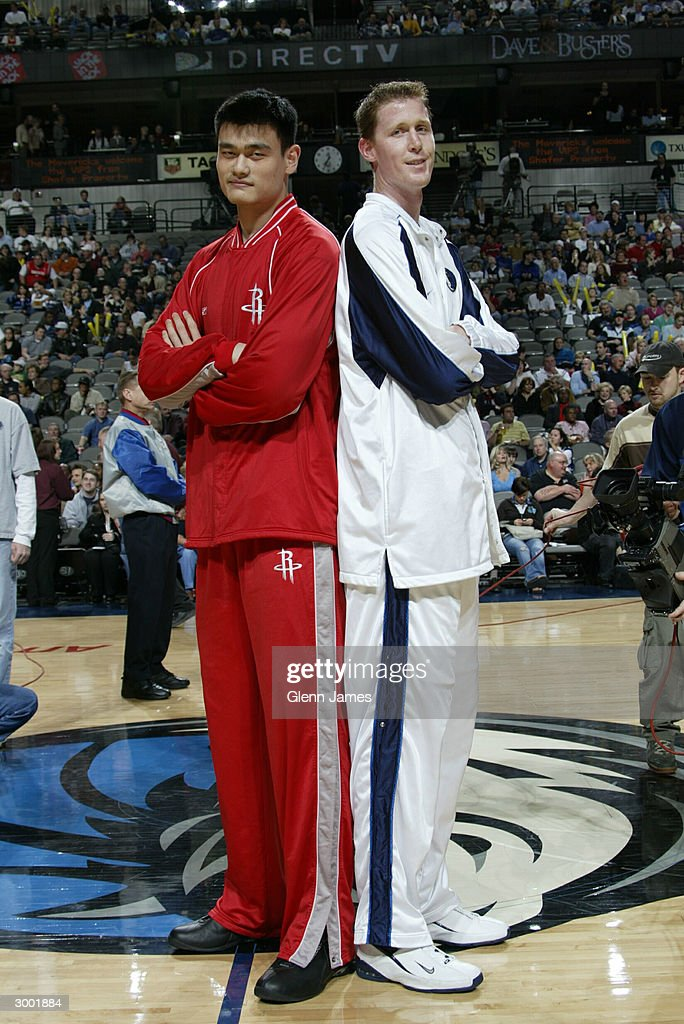 Shawn Bradley #44 of the Dallas Mavericks stands with Yao Ming #11 of the Houston Rockets on February 21, 2004 at the American Airlines Center in Dallas, Texas.