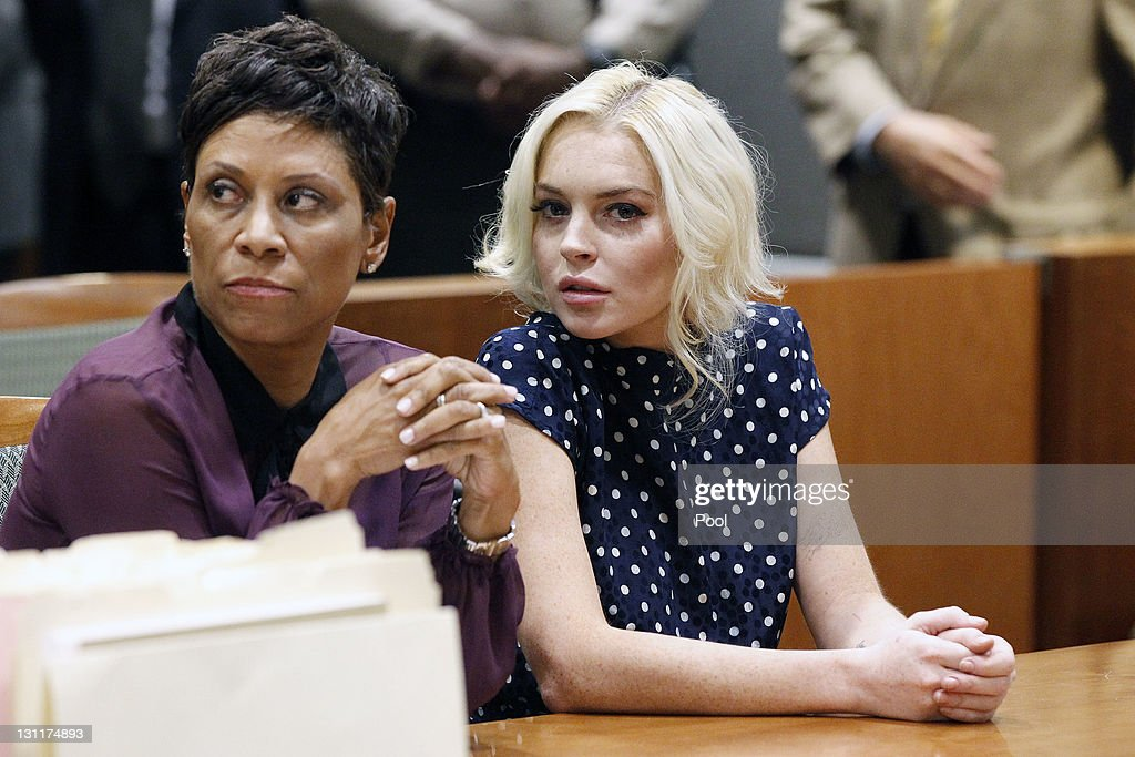 Shawn Chapman Holley Lohan's attorney and Lindsay Lohan sit in court during Lohan's probation violation hearing at the Airport Courthouse on November...
