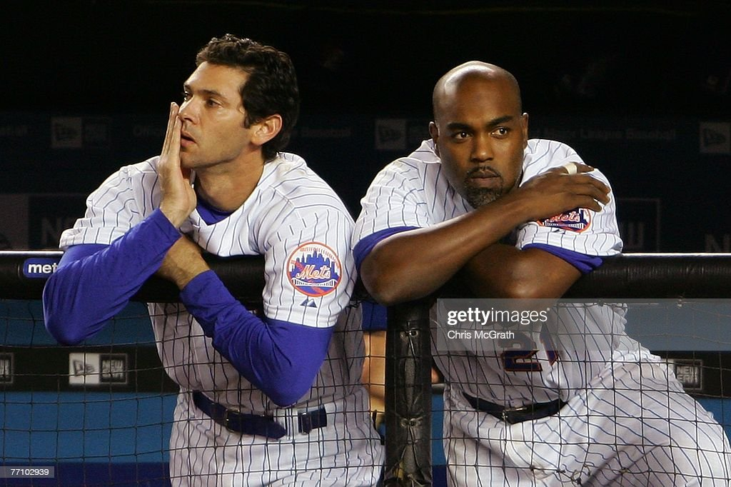 Shawn Green and Carlos Delgado of the New York Mets watch on from the dugout in the bottom of the nineth inning against the Florida Marlins during...