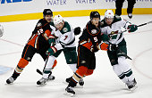 Shawn Horcoff of the Anaheim Ducks and Korbinian Holzer of the Anaheim Ducks battle for position with Chris Porter of the Minnesota Wild and Ryan...