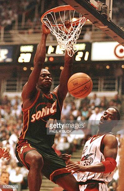 Shawn Kemp of the Seattle Supersonics slams home two of his gamehigh 24 points as Houston Rockets Kevin Willis looks on during first half action at...