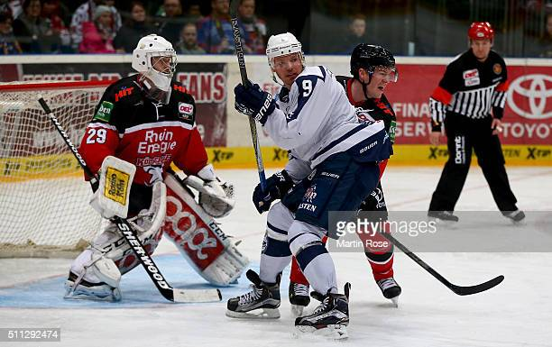 Shawn Lalonde of Koelner Haie and Morten Madsen of Hamburg Freezers battle for the puck during the DEL Ice Hockey match between Koelner Haie and...