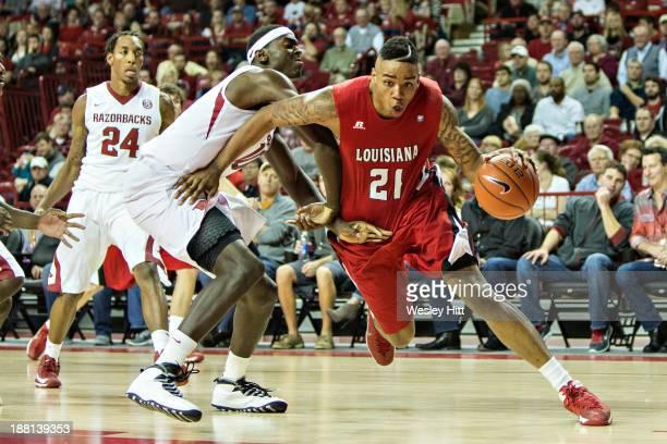 Shawn Long of the Louisiana Ragin' Cajuns drives to the basket against Bobby Portis of the Arkansas Razorbacks at Bud Walton Arena on November 15...