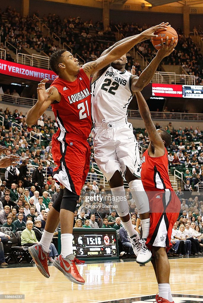 Shawn Long #21 of the Louisiana-Lafayette Ragin' Cajuns tries to block a first half shot of Branden Dawson #22 of the Michigan State Spartans at the Jack T. Breslin Student Events Center on November 25, 2012 in East Lansing, Michigan.
