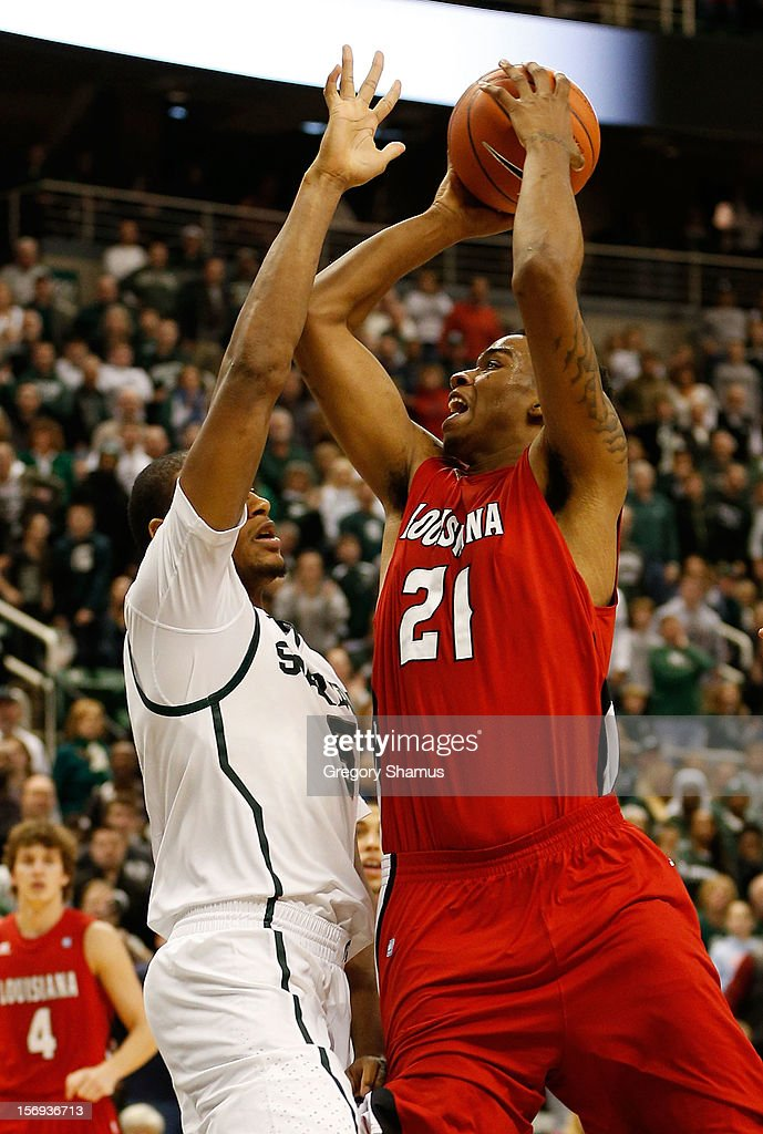 Shawn Long #21 of the Louisiana-Lafayette Ragin' Cajuns tries to get a shot off over Adreian Payne #5 of the Michigan State Spartans at the Jack T. Breslin Student Events Center on November 25, 2012 in East Lansing, Michigan. Michigan State won the game 63-60.